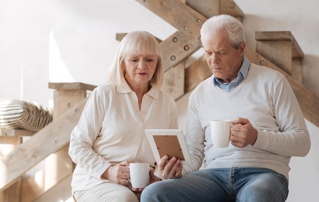 Coppia infelice anziana triste seduti insieme e guardando la foto mentre si prende il tè