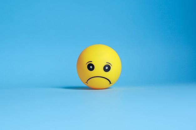Emoticon triste isolato su priorità bassa blu