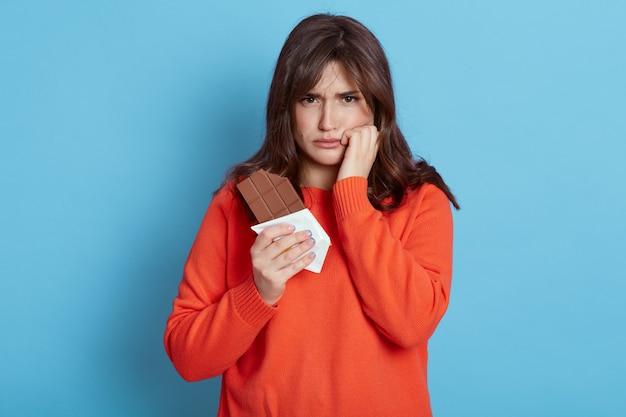 Triste donna europea dai capelli scuri che indossa abiti casual in posa isolata sopra la parete blu, guardando con espressione sconvolta, ha mal di denti, soffre di dolore, tiene il pugno sulla guancia.