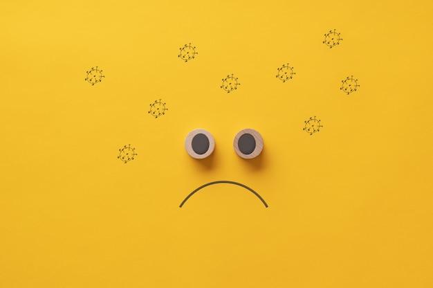 Faccia triste fatta di cerchi di legno tagliati circondati da molecole di coronavirus disegnate a mano.