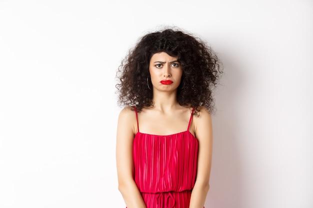 Triste accigliata signora in abito rosso che si lamenta, sembra gelosa o sola, in piedi sconvolta su sfondo bianco. copia spazio