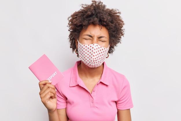 La donna dai capelli ricci frustrata triste tiene il passaporto non può viaggiare all'estero a causa della pandemia di coronavirus e la quarantena indossa la maglietta rosa casuale della maschera facciale usa e getta isolata sopra il muro bianco
