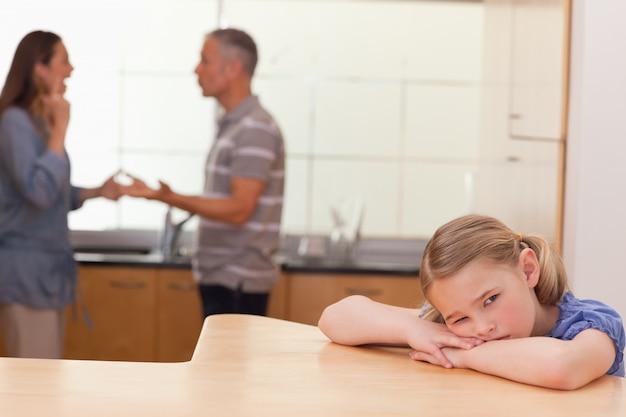 Ragazza triste che ascolta i suoi genitori che si adattano