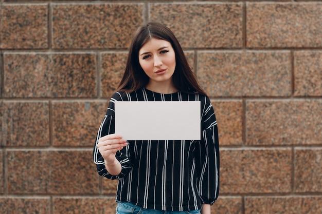 La ragazza triste tiene in mano il libro bianco sullo sfondo di pietra. giovane donna con foglio bianco modello vuoto con spazio vuoto.