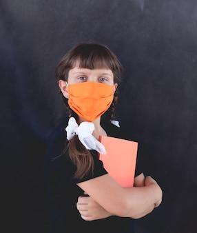 La ragazza triste con una maschera arancione su sfondo nero con un taccuino torna a scuola