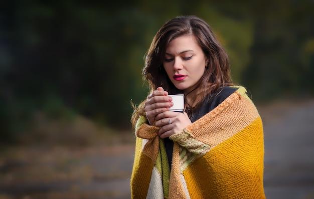 Ragazza triste all'aperto con una tazza di caffè (tè) e avvolta in una calda coperta.