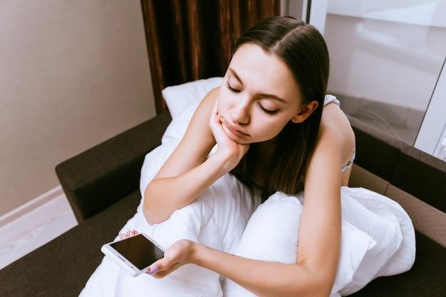 Ragazza triste seduta sul letto e guardando il telefono
