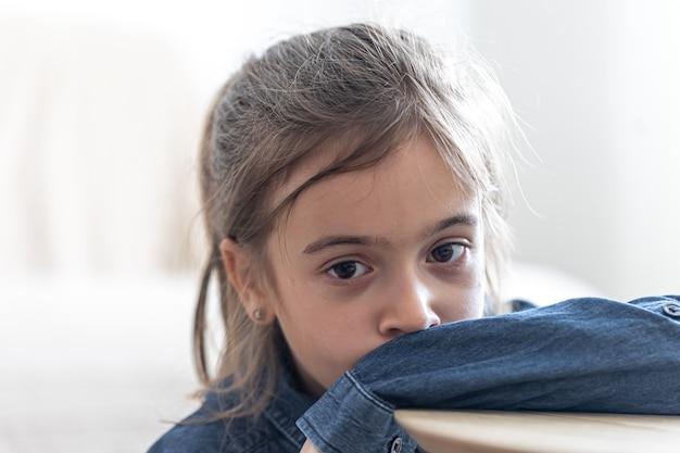 Ragazza triste seduta al tavolo a scuola, torna al concetto di scuola.