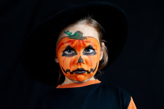 Ragazza triste con trucco di zucca sul viso per halloween, con un cappello nero, solitudine e tristezza in vacanza.