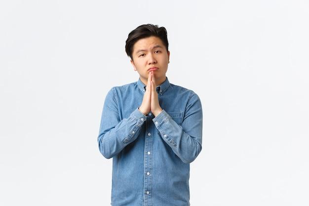 Triste cupo maschio asiatico che chiede aiuto, implorando favore, in piedi su uno sfondo bianco e si tiene per mano insieme per supplicare, supplicare, prestare denaro da un amico, scusarsi.