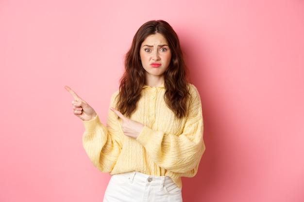 Ragazza bruna triste e cupa che si lamenta di un cattivo testo promozionale, puntando le dita da parte a sinistra, mostrando banner con espressione delusa, in piedi su sfondo rosa.
