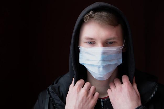 Un giovane triste e bello si protegge dal coronavirus con una mascherina medica, guarda in basso e regola il cappuccio della giacca. l'epidemia virale sta arrivando, covid-19
