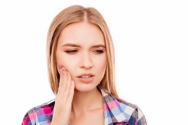 Donna malata triste che ha mal di denti e che tocca la guancia