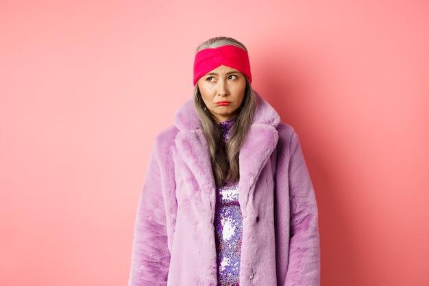 Donna anziana asiatica triste e indecisa con un cappotto di pelliccia sintetica alla moda che guarda a sinistra e imbronciata sconvolta, in piedi su sfondo rosa.