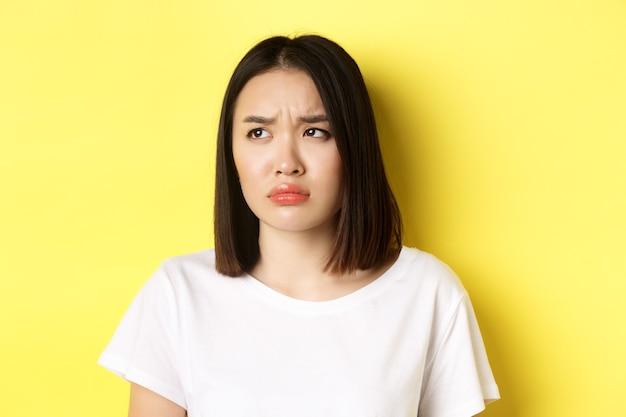 Ragazza asiatica triste e gelosa che tiene il broncio, si acciglia e guarda a sinistra con la faccia sconvolta, in piedi su uno sfondo giallo