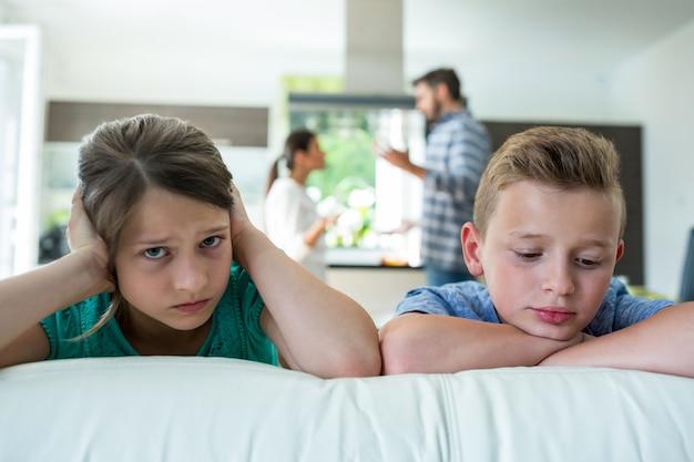 Bambini tristi che si appoggiano sul divano mentre i genitori litigano
