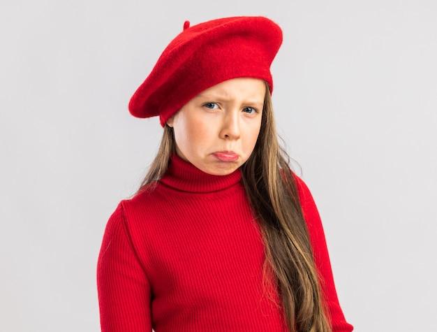 Triste bambina bionda che indossa un berretto rosso guardando la parte anteriore isolata sul muro bianco con spazio di copia