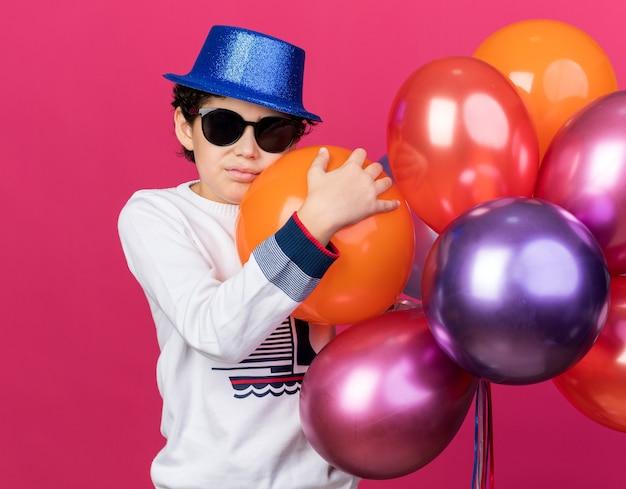 Ragazzino triste che indossa un cappello da festa blu con occhiali che tengono palloncini isolati su una parete rosa