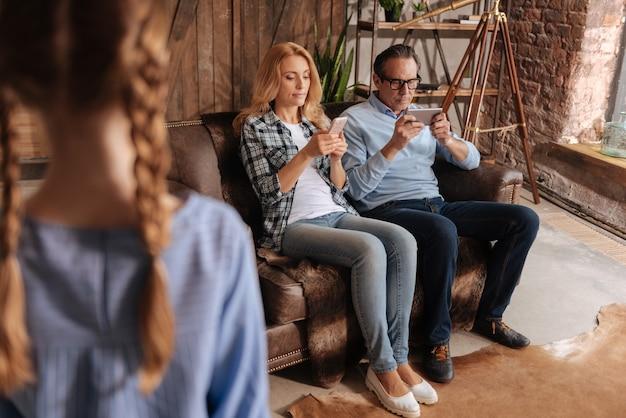 Triste ragazzino carino in attesa dell'attenzione dei genitori a casa ed esprime tristezza mentre gli adulti usano gli smartphone ed esprimono apatia