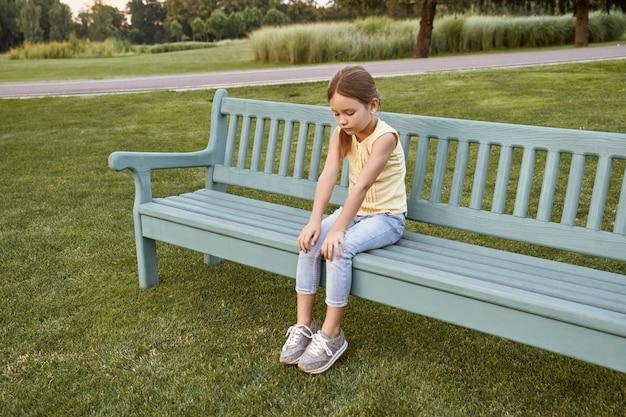 Triste bambina seduta sulla panchina nel parco in una calda giornata in attesa di genitori all'aperto