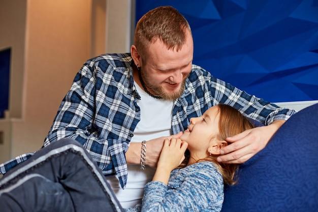 Triste bambina seduta sul divano, il padre si adatta e saluta la figlia che si diverte in soggiorno, a casa. famiglia felice.