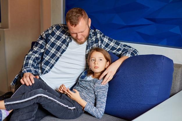 Bambina triste che si siede sul divano, il padre si adatta e applaude la figlia divertendosi in salotto, a casa