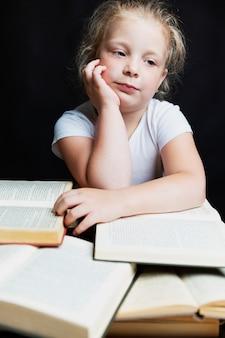 Bambina triste che si siede con una pila di libri. conoscenza ed educazione. sfondo nero. verticale.