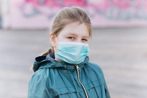 Bambina triste in protettivo medico sterile dalla maschera del virus all'aperto. assistenza sanitaria, epidemia, pandemia, concetto di malattia