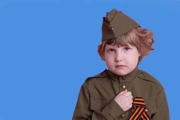 Bambina triste nell'uniforme dei soldati sovietici durante la guerra mondiale