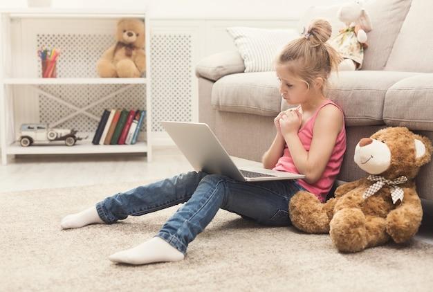 Bambina triste che guarda film scusa ragazza seduta sul pavimento, a casa da sola, a guardare cartoni animati sul laptop con il suo amico giocattolo orsacchiotto, simpatia per bambini e concetto di sincerità, spazio copia