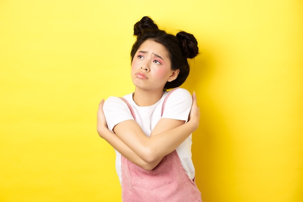 Ragazza asiatica sola triste che osserva da parte con la faccia sconvolta e cupa, che si abbraccia, sognando l'amore e il ragazzo, giallo.