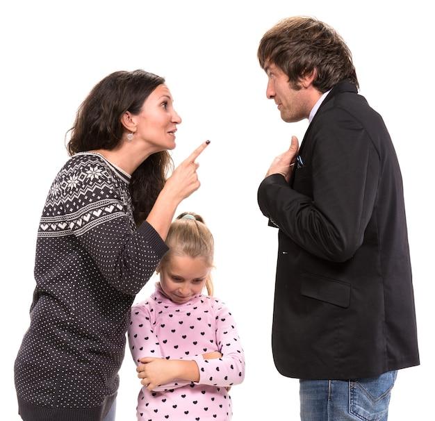 Ragazza dall'aspetto triste con i suoi genitori in lotta su un muro bianco