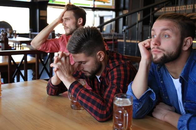 Tifosi maschi tristi che guardano la partita al bar e bevono birra. Foto Premium