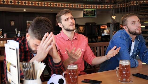 Tifosi maschi tristi che guardano la partita al bar e bevono birra.