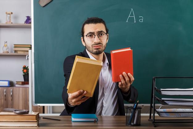 Insegnante maschio triste con gli occhiali che tiene fuori il libro seduto al tavolo con gli strumenti della scuola in classe