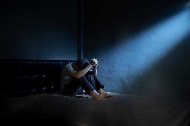 Uomo triste sul letto nella camera oscura