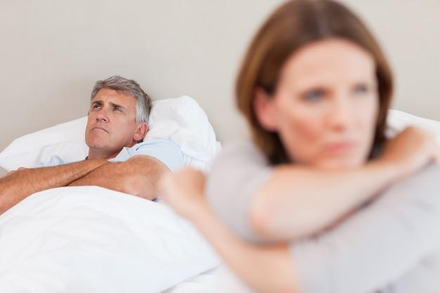 Triste uomo a letto con sua moglie in primo piano