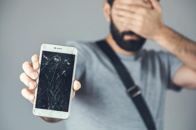 Telefono rotto della mano dell'uomo triste su gray