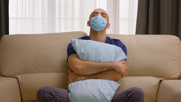 Uomo triste che tiene un cuscino durante la quarantena del coronavirus seduto sul divano con indosso una maschera.
