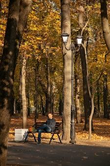 L'uomo triste è seduto su una panchina in un parco cittadino autunnale con un mazzo di fiori e aspetta a lungo. un appuntamento fallito