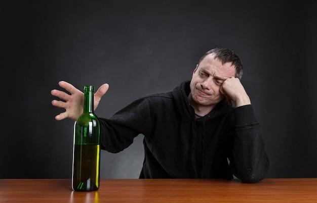 L'uomo triste sta prendendo una bottiglia di alcol
