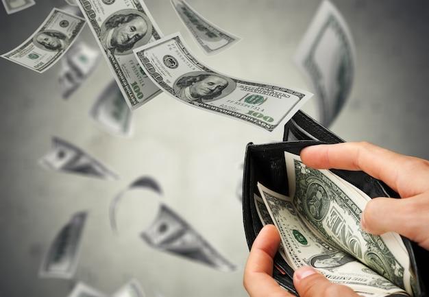 Uomo triste che guarda il suo portafoglio con banconote in dollari che volano via