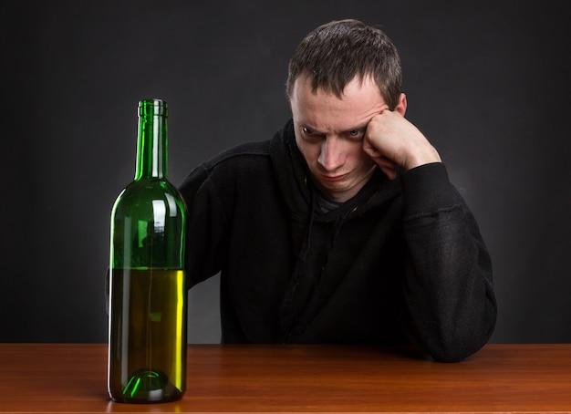 L'uomo triste guarda la bottiglia di vino