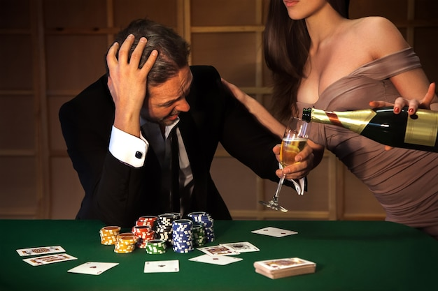 Uomo triste perso a poker e una cameriera con grandi tette in un vestito con un profondo dekolte versa champagne in un bicchiere. a seconda del concetto di gioco d'azzardo e casinò