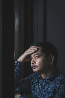 Uomo triste che pensa e guarda fuori dalla finestra
