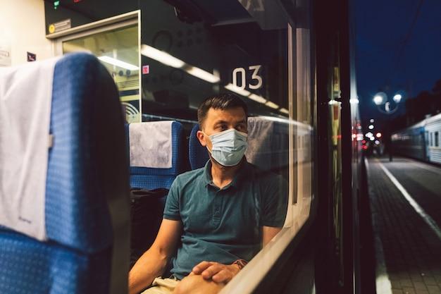 L'uomo triste indossa la maschera protettiva in treno
