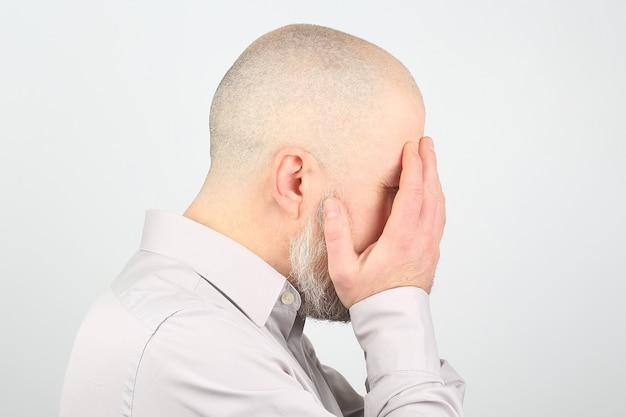 Uomo triste con le mani chiuse il viso su sfondo bianco