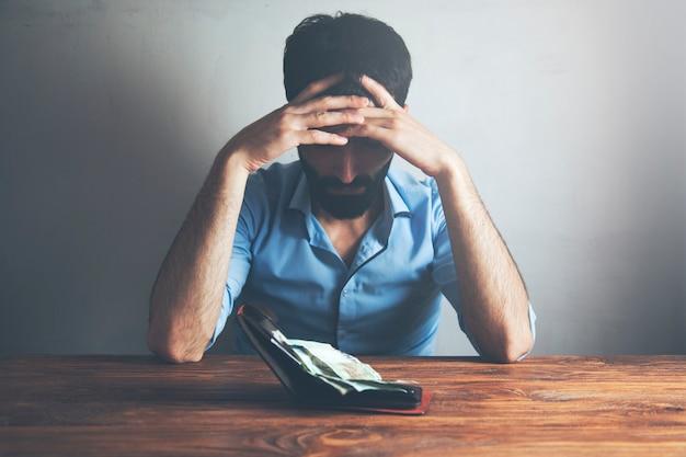 Uomo triste con portafoglio e soldi