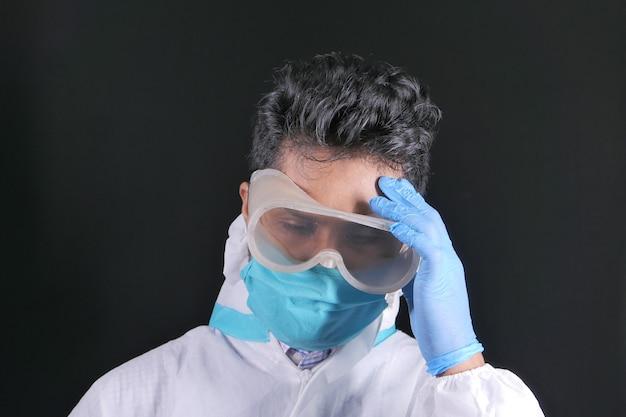 Medico maturato triste che copre il viso con le mani isolate sul nero