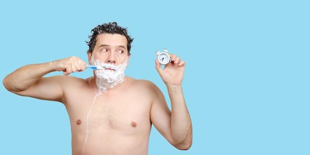 Triste uomo bianco di mezza età tiene lo spazzolino da denti in bocca, radersi, lavarsi la testa, guarda la sveglia in mano ed essere in ritardo al lavoro o una riunione o dormito troppo su sfondo blu, copia spazio per il testo